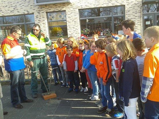 De koninklijke knikkertegel wordt gelegd. Even na dit moment namen schooldirecteur Jan Peters en twee leerlingen van basisschool Den Bussel in Kaatsheuvel de Koningstegel in gebruik.