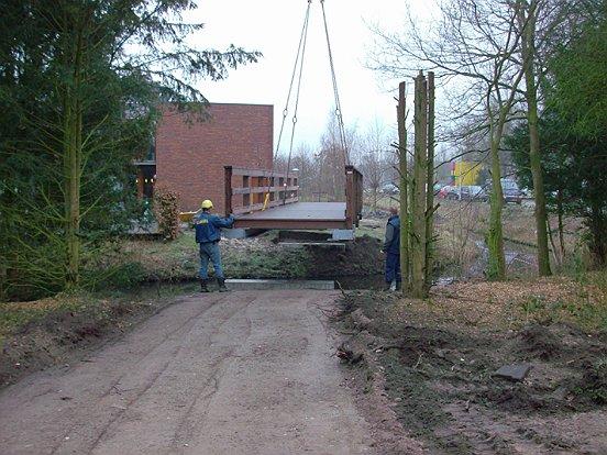 Plaatsen van een brug in een zorgwandelpark.